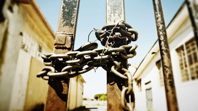 The gate to a disused industrial building is barred, chained and locked.