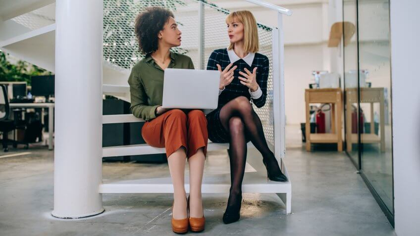 Shot of two businesswomen sitting on the stairs talking.