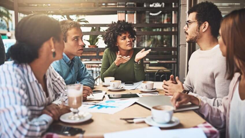 Shot of a group of focused young work colleagues having a discussion at a meeting together while being seated around a table.