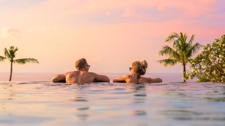 Romantic couple looking at beautiful sunset in luxury infinity pool.
