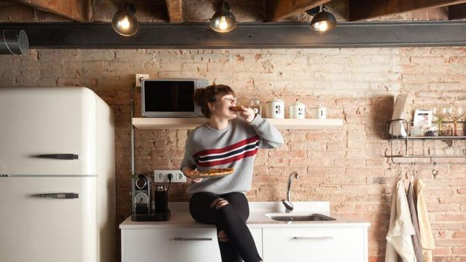 Beautiful girl eating pizza in a modern kitchen.