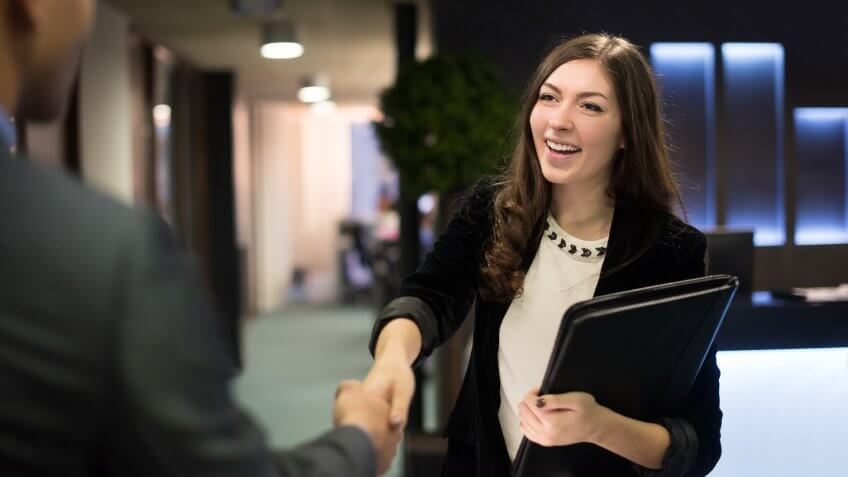 young woman arrives at her interview , resume under her arm greeting her interviewer.