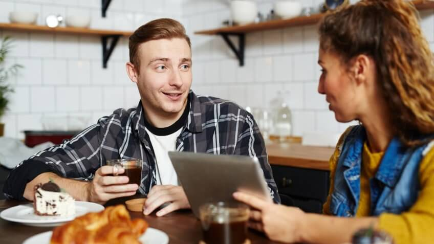 Smiling handsome young man talking to friend and drinking coffee from mug at home, they using tablet to watch video.