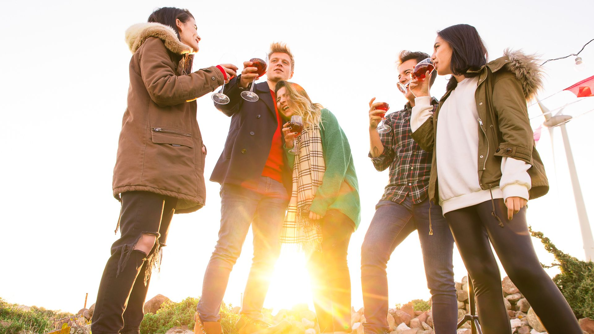 Cheerful friends having fun by the campfire during the autumn.