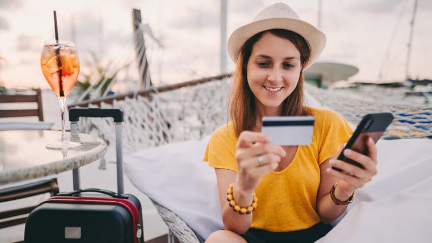 Young woman making credit card payments from smartphone.