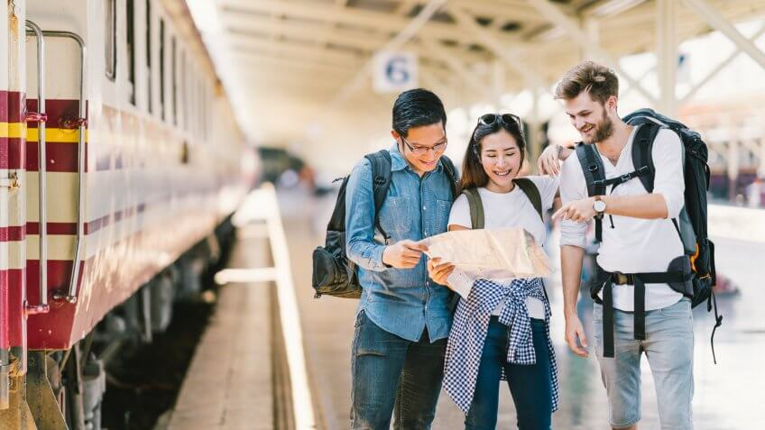 Multiethnic group of friends, backpack travelers, or college students using generic local map navigation together at train station platform.
