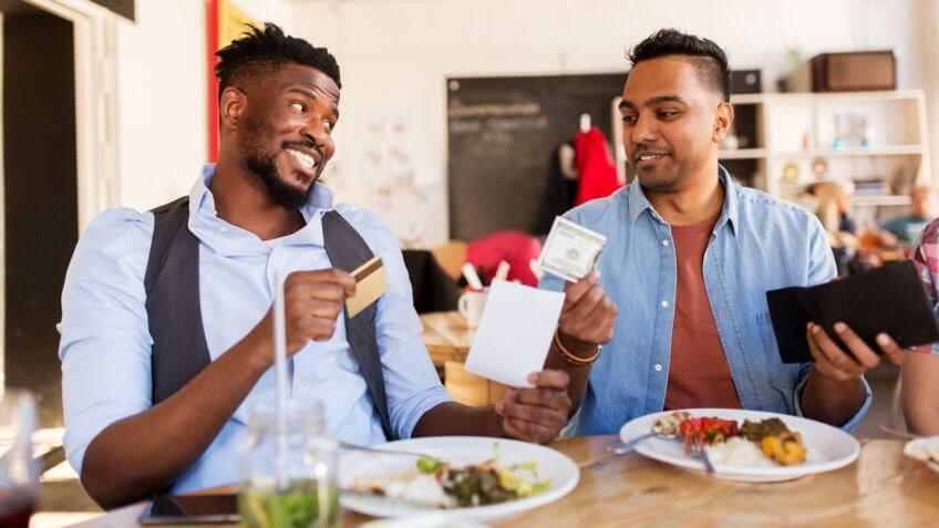 happy friends with money and credit card paying bill for food at restaurant