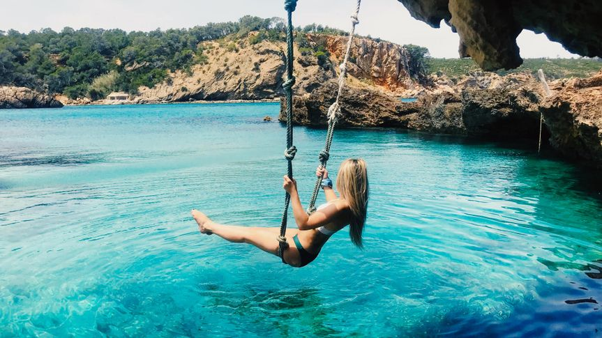 lady swinging over ocean water in Ibiza island of Spain