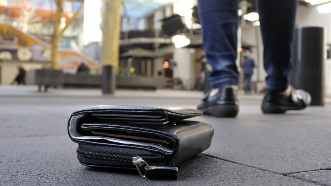 Woman walking away after losing her wallet on city street.