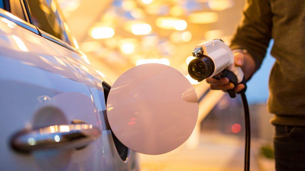 Man charging electric car.