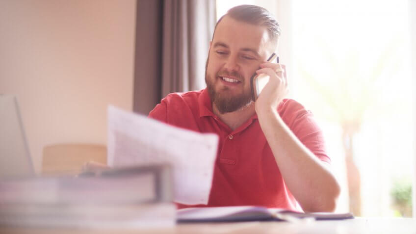 A young male possibly a single parent or small business owner sits at home talking to the bank or finance company on the phone.