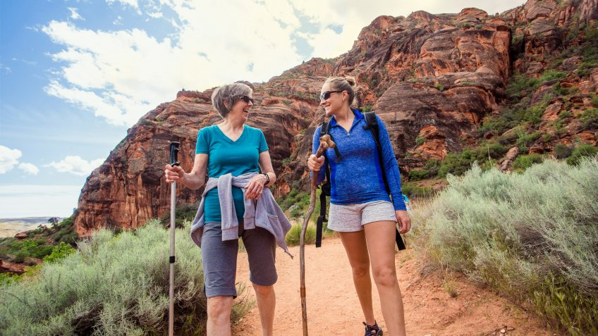 Two happy women hiking together in a red rock sandstone canyon in the deserts of Utah on an adventure vacation.