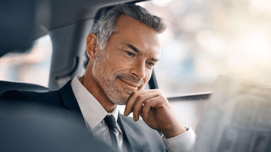 Cropped shot of a handsome mature businessman reading the paper while sitting in the backseat of a car during his morning commute.