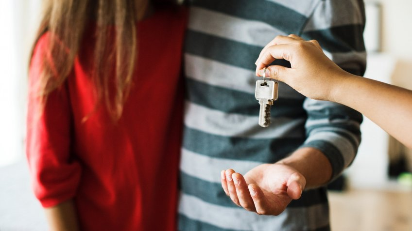 person hanging keys to man's hand standing next to woman