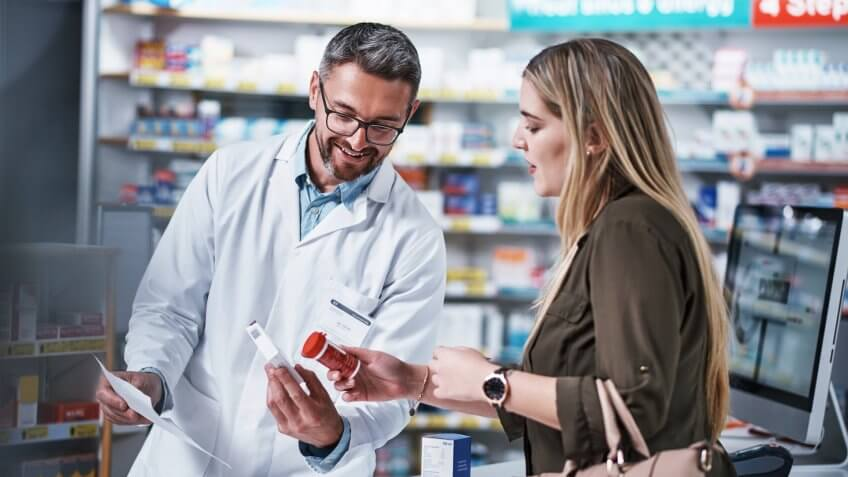 Shot of a mature pharmacist assisting a young woman in a chemist.