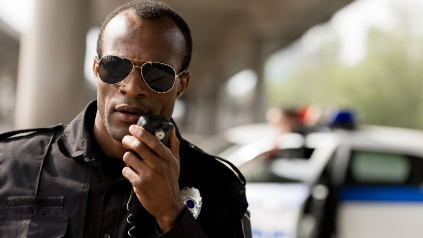 african american police officer talking by walkie-talkie radio set.