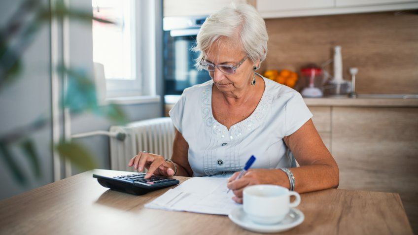 Serious elderly woman with calculator sitting at table.