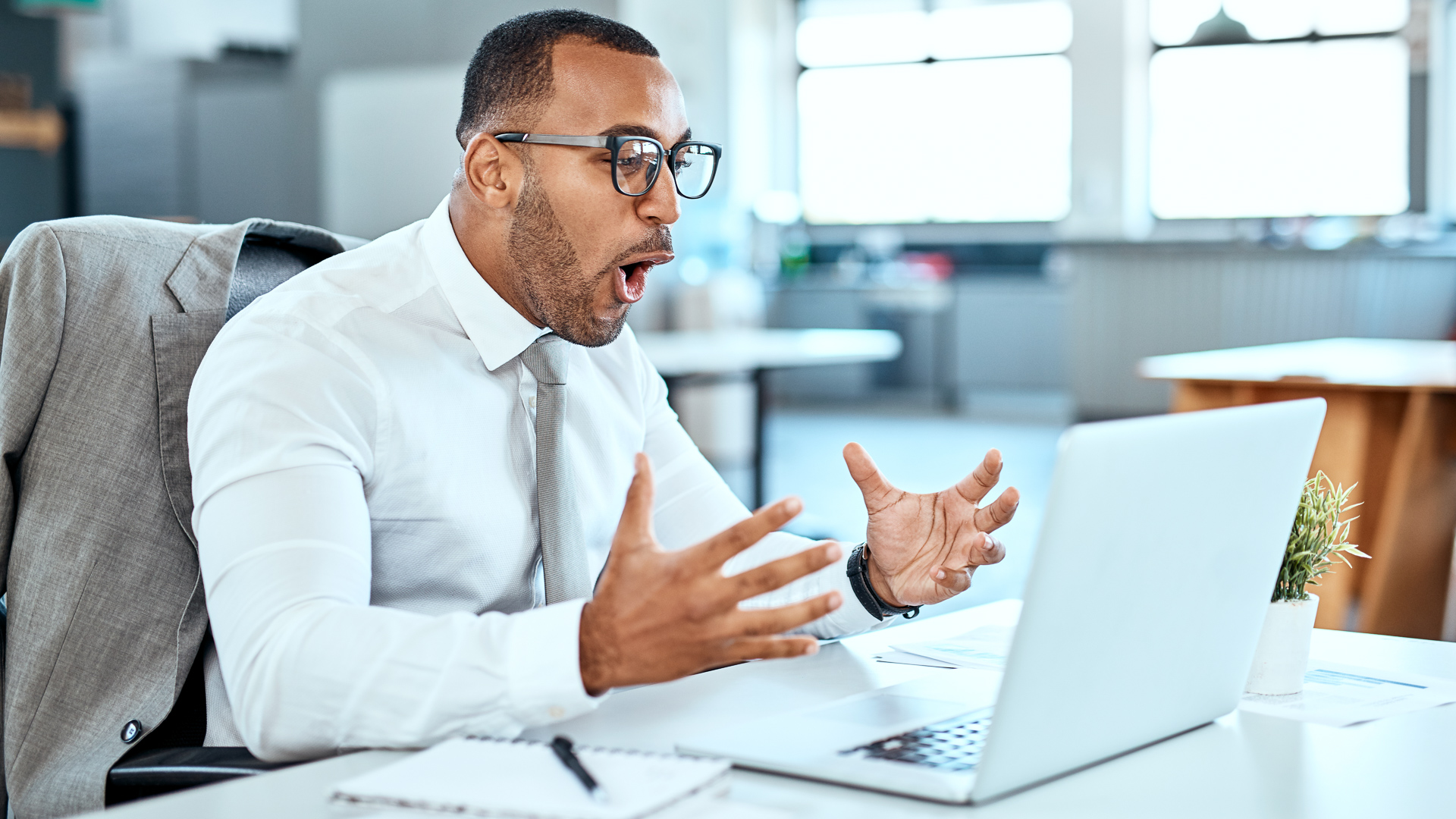 Shot of a young businessman looking surprised while working on a laptop in an office.