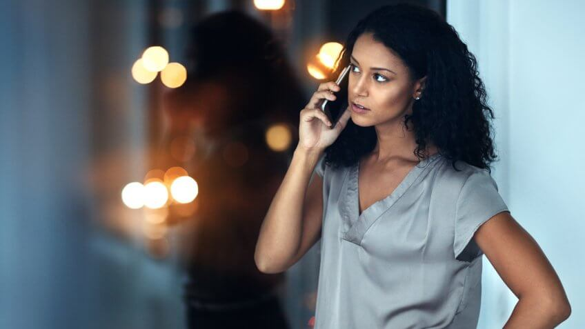 Shot of a young businesswoman talking on a mobile phone during a late night at work.