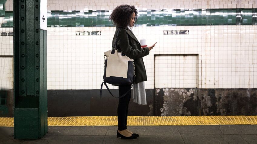 Young woman waiting for the subway train in New York, USA.