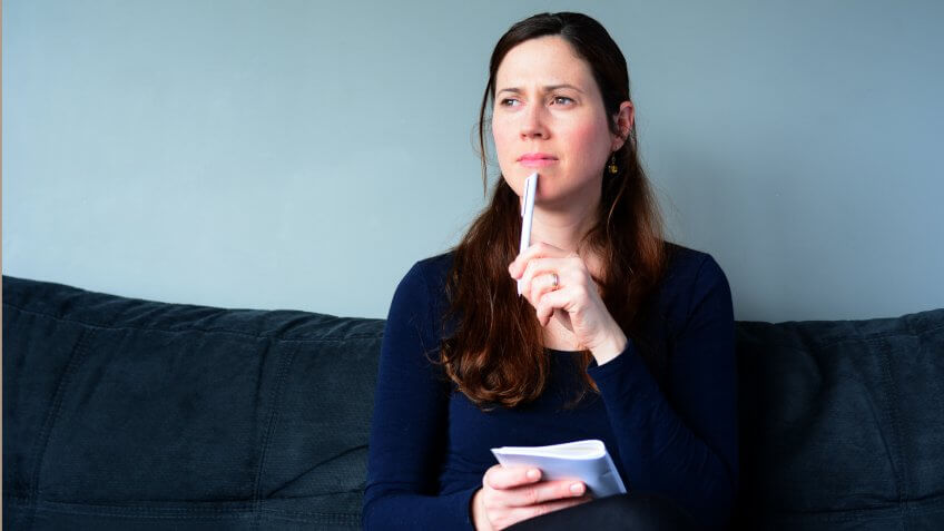 Young woman in her thirties (30s) hold a notepad thinking about to do list at home.