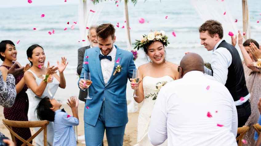Cheerful multiracial newlyweds at beach wedding ceremony