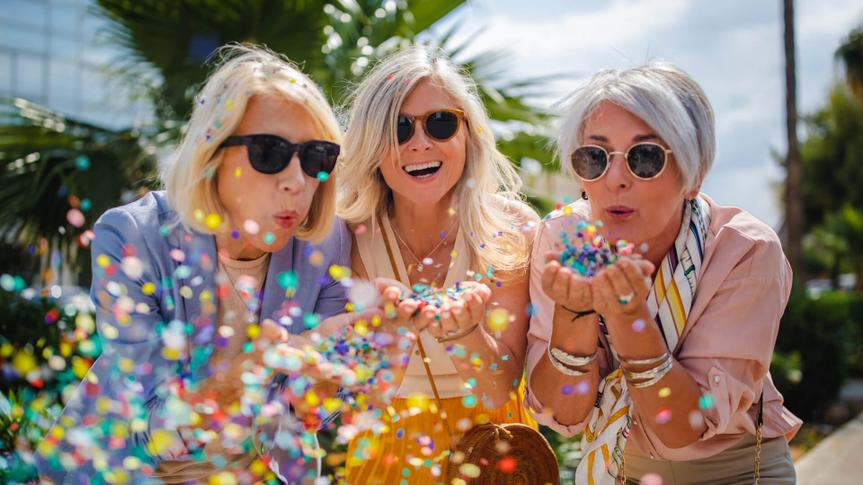 Fashionable mature friends having fun and celebrating by blowing colorful confetti in city street.