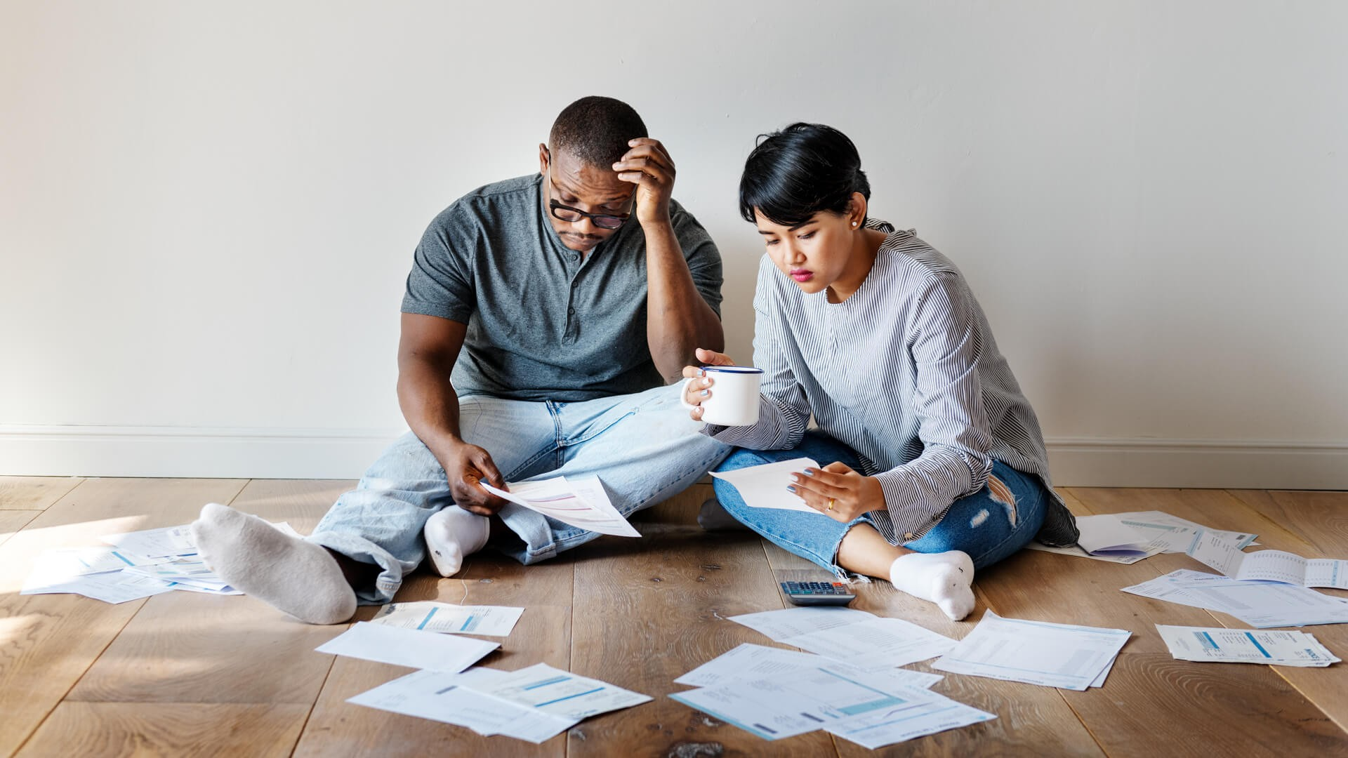 Couple-sitting-on-floor-managing-finance-documents