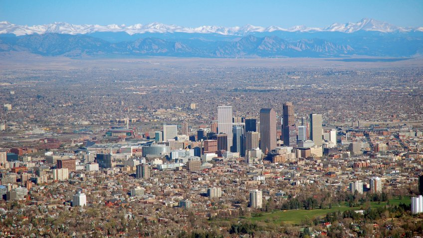 Aerial photo of downtown Denver, Colorado with the Rocky Mountains in the background.