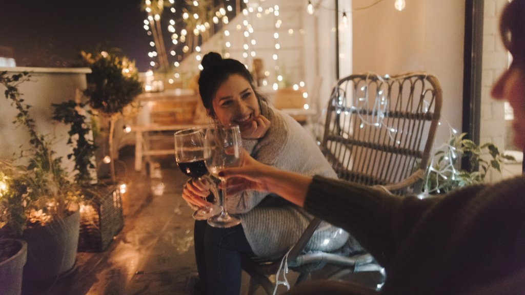 Young smiling woman enjoying in good wine and great company on the open terrace of her loft apartment.