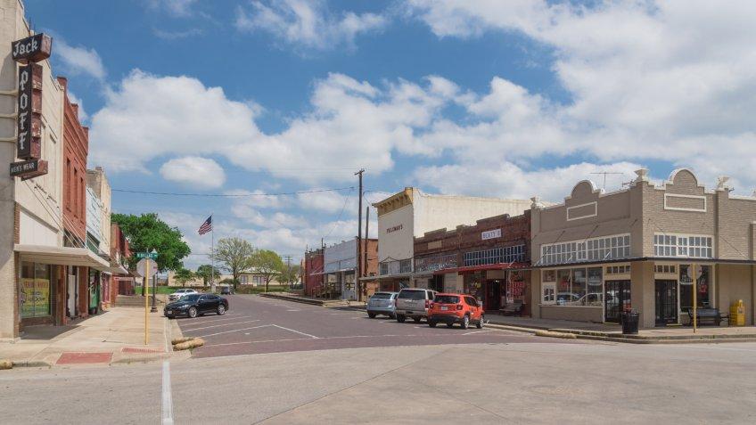 ENNIS, TX, USA-MAR 31, 2018:Historic vintage building, street at downtown Ennis cloud blue sky.