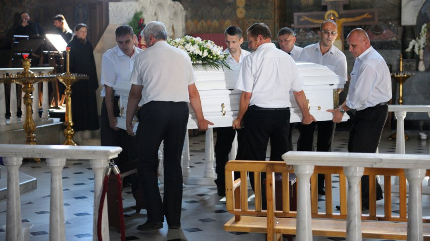 funeral service workers carrying a casket