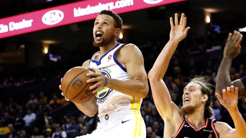 Stephen Curry of Golden State Warriors slam dunks