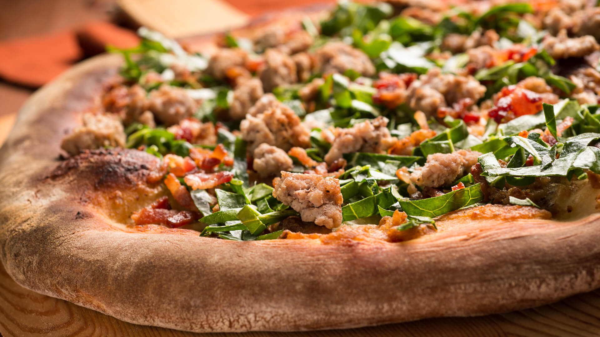 Gourmet pizza with sausage and spinach.