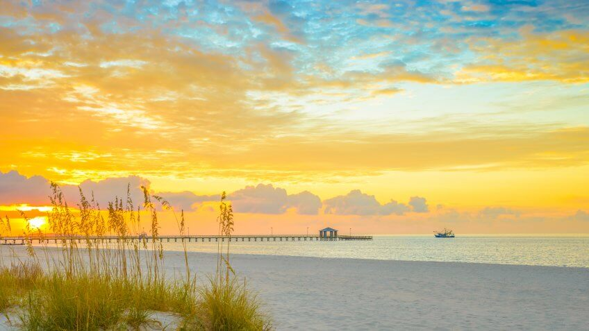 Gulfport Mississippi beach, dramtic golden sunrise, pier, shrimp boat, on the Gulf of Mexico.