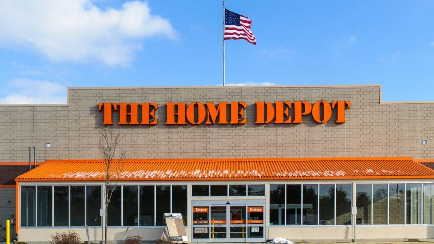 """Wareham, Massachusetts, USA-January 7, 2013: An American flag flies over the entrance and outside facade of a large Home Depot store that sells a full range of building matrerials and home products."