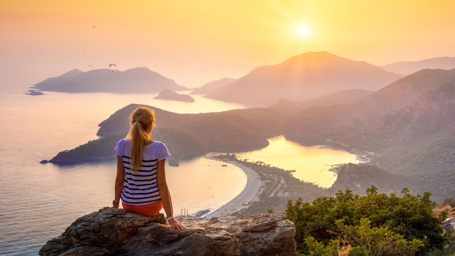 Young woman sitting on the top of rock and looking at the seashore and mountains at colorful sunset in summer.