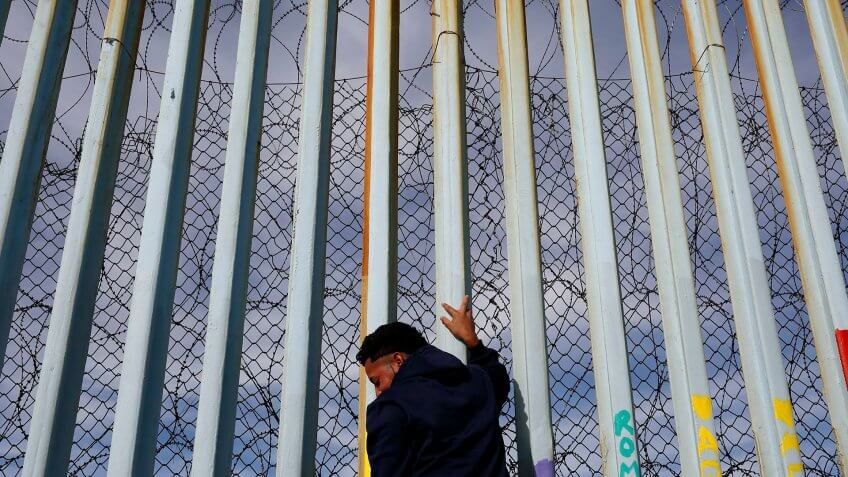 A man holds on to the border wall along the beach, in Tijuana, Mexico.
