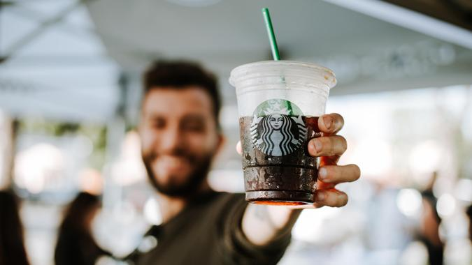 Millennial holding up a cup of Starbucks iced coffee
