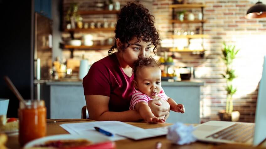 Close up of a mother having breakfast and doing bills with her daughter.