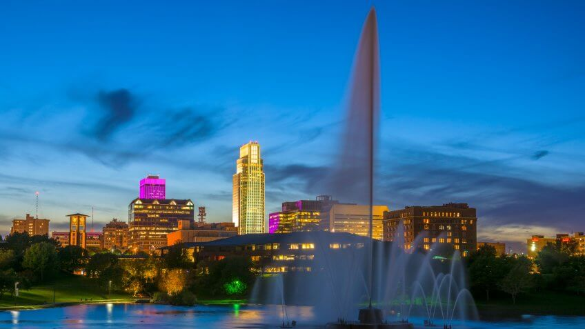 Downtown Omaha skyline with the Heartland of America Park, including a large fountain, in the foreground.