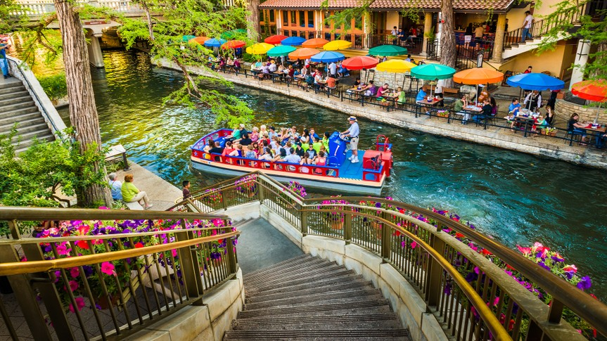 San Antonio, Texas, USA - April 14, 2013: Tourists riding in tour boat and eating at restaurants along The Riverwalk in San Antonio Texas.