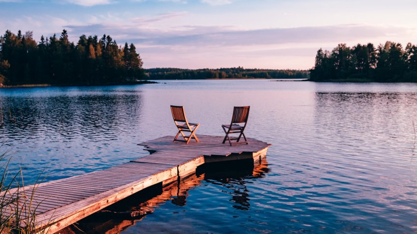Two wooden chairs on a wood pier overlooking a lake at sunset in Finland.