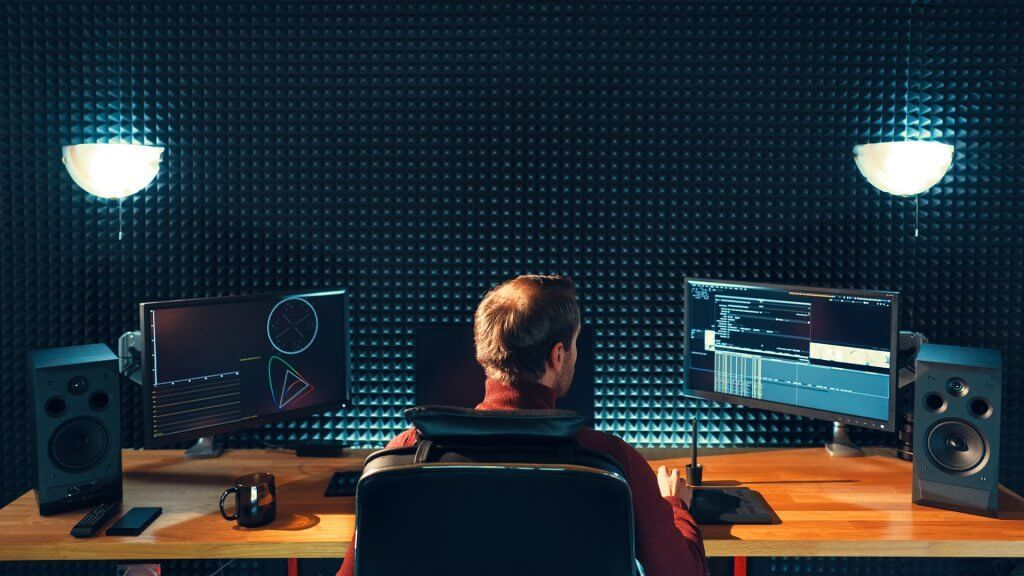 video editor at a desk with two monitors and speakers