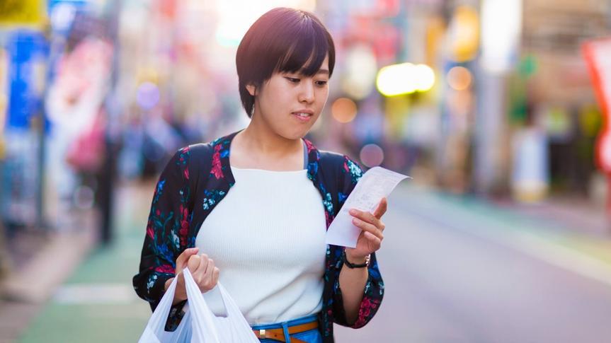 woman checking shopping receipt