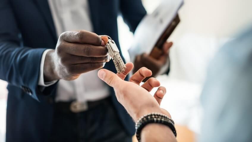 Real estate agent handing the house key to a client.