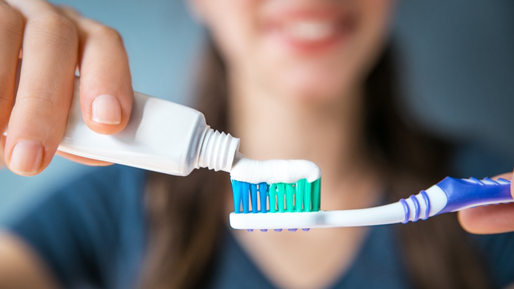 applying toothpaste to toothbrush to brush teeth