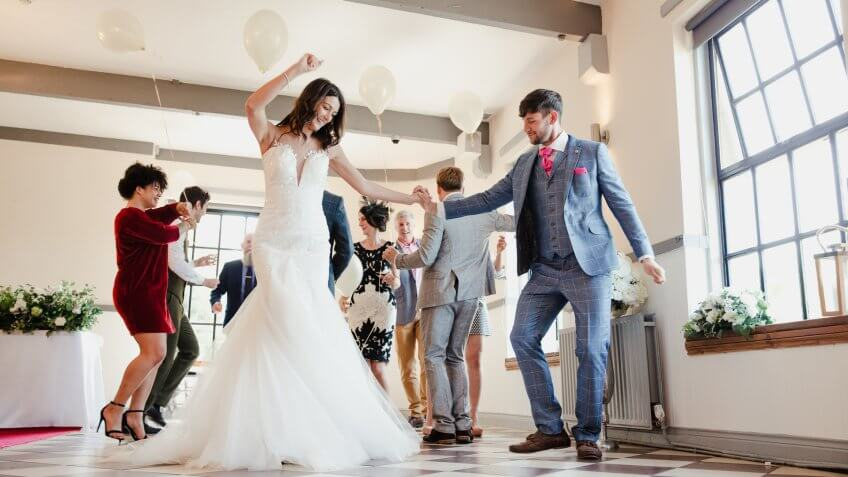 newlywed couple dancing with their guests on the dance floor