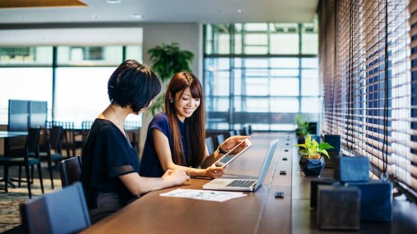 Business as usual in a modern Japanese or Korean office where two businesswomen working together on financial statements, budget clarification and project management.