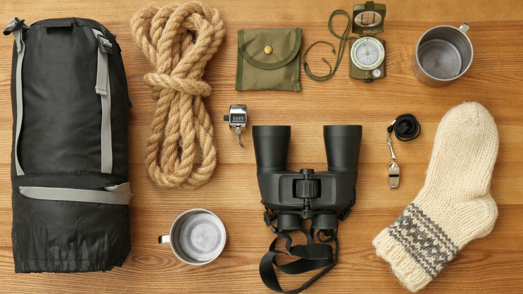 Flat lay composition with sleeping bag and camping equipment on wooden background - Image.